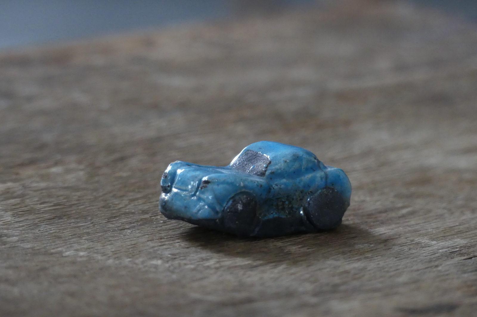petite voiture bleu sur fond bois raku