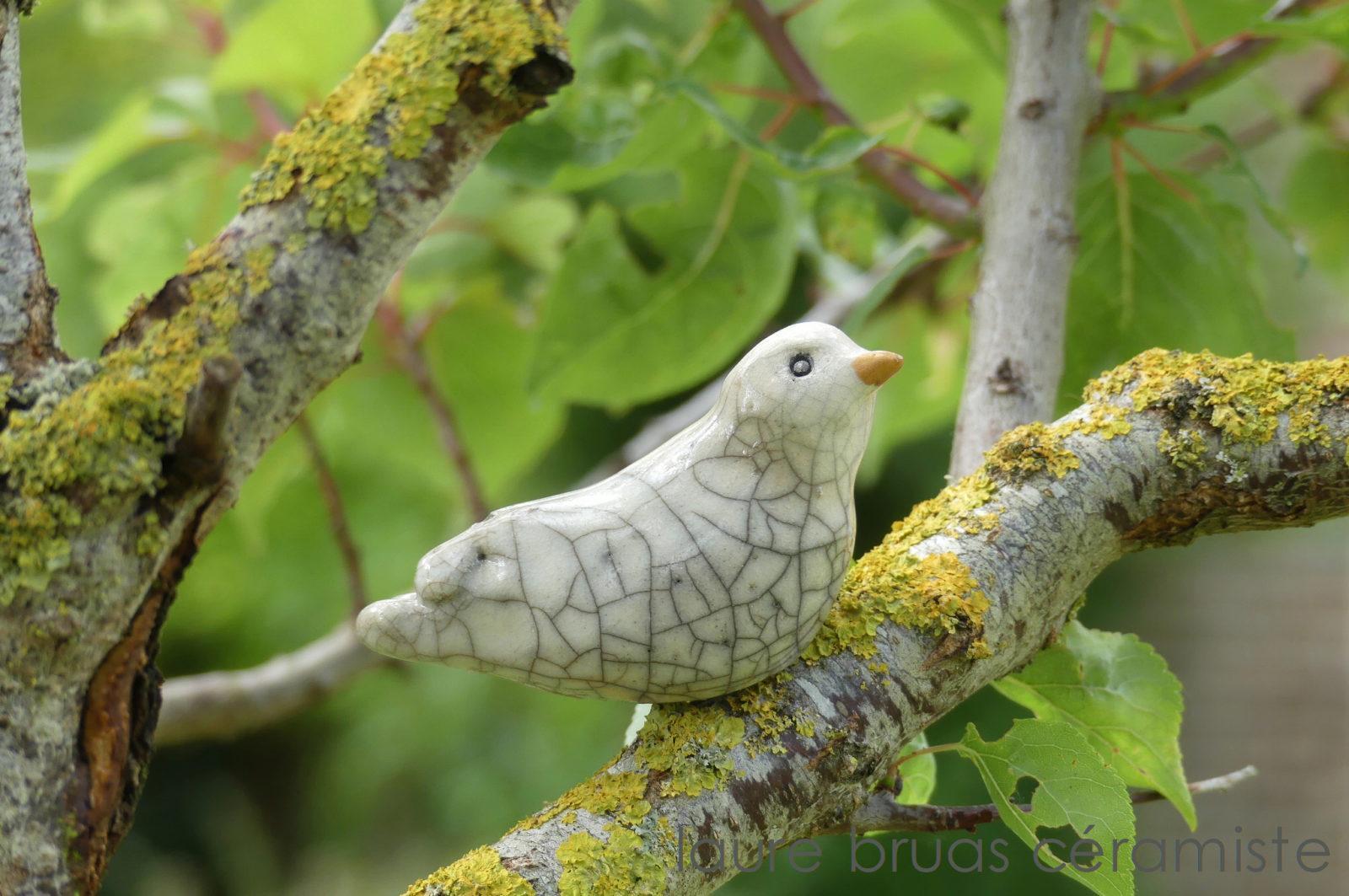 Colombe blanche craquelée en céramique raku posée sur une branche d'arbre