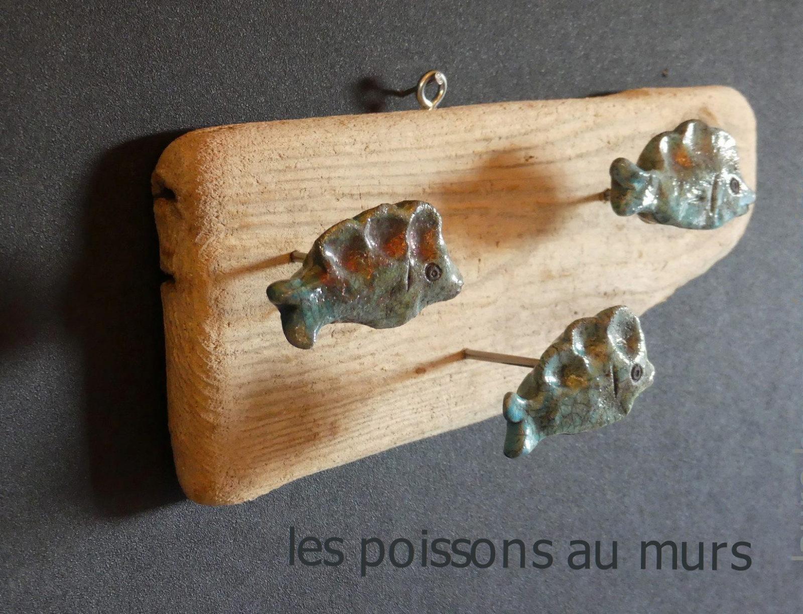 trois poisson en céramique raku piqués sur le coté sur une planche de bois flotté et accrochés sur un mur noir